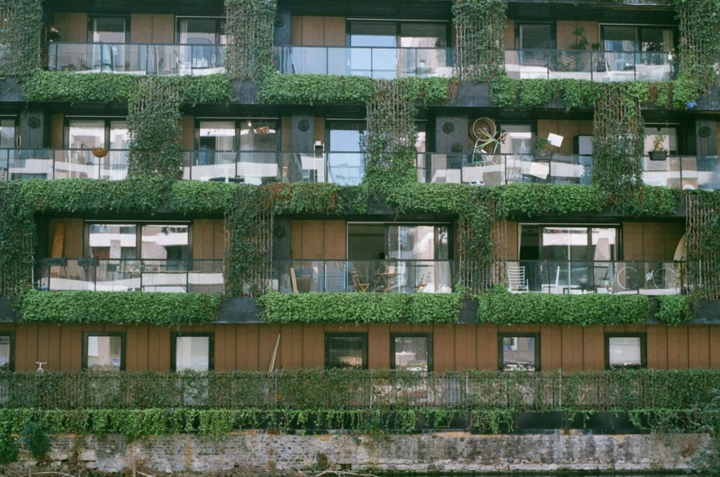 Ext. Day. Side of a residential building on an East London canal side. We can see balconies of many different apartments. The general look is rich hipster gentrification. The whole side is covered in ivies and its main colour is a brown attempt to resemble wood.