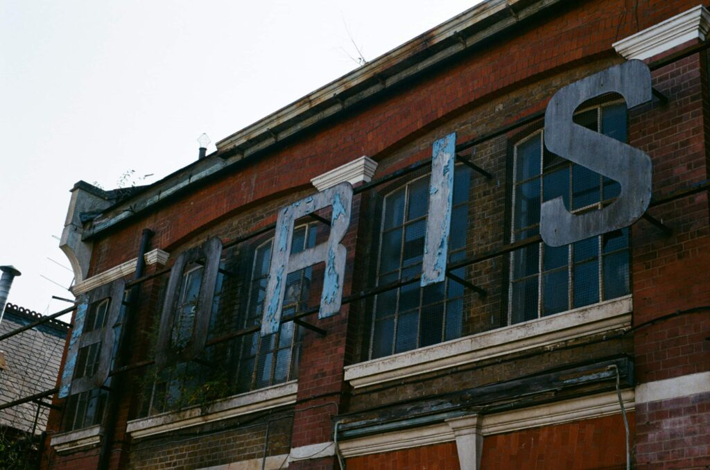 Ext. Day. Photo take from below and on the side of a sign of an abandoned warehouse. The letters we can read in the photo make up the name BORIS. There's still some blue paint attached to them giving an overall punk-ish look to the composition.