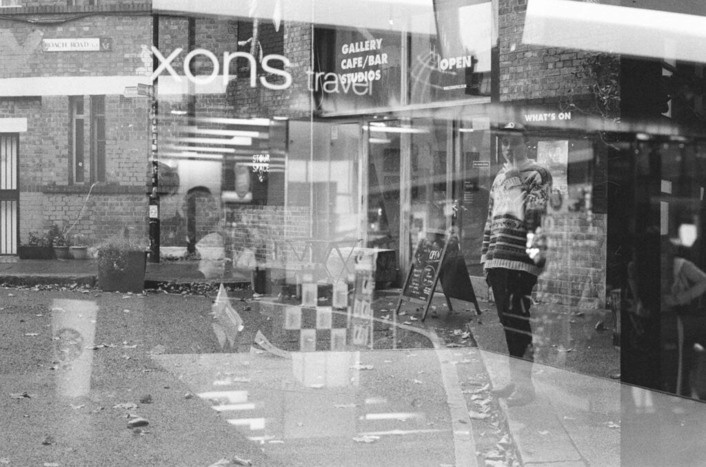 Ext. and Int. Day. Black and white double exposed photo. On one exposure, we have a man standing on the side of the street, smoking a cigarette. On the other exposure, we have signs from shops in an airport.