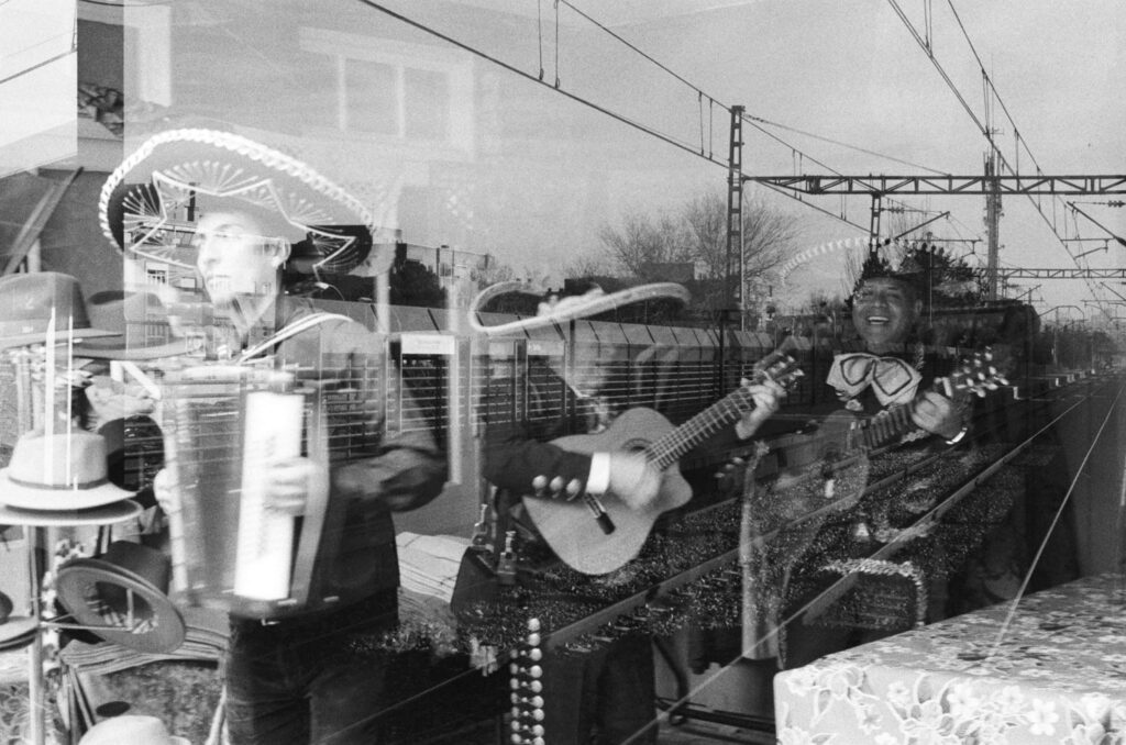 Ext. Day. Black and white double exposed photo. On one exposure we have a group of mariachi performing. On the other exposure we have a long and empty railroad.