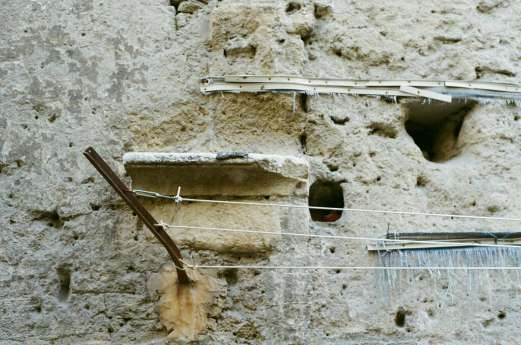 Ext. Day. Detail of a side of a building in the Ancient City Centre of Naples. It is made of not-at-all-maintained tuff. Stuck in it, there's a piece of metal with some strings attached. An homemade drying rack.