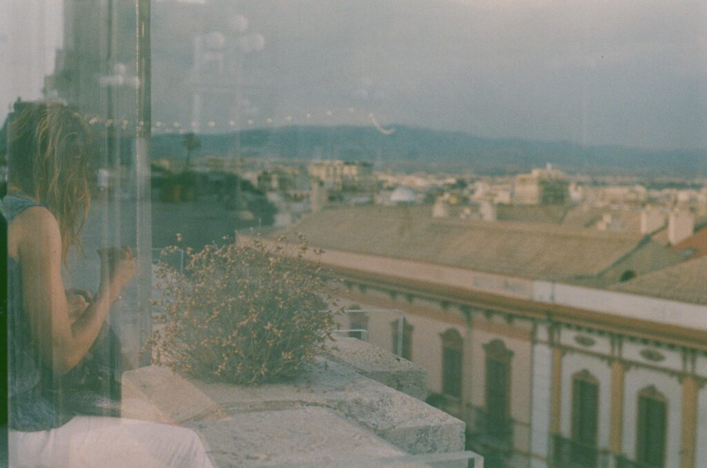 Ext. Day. Scenic photo of Cagliari taken through a glass wall put on top of a parapet. On the other side of the glass, we can see a wild dry bush growing on the parapet itself. Reflected on the glass wall, a person whose face is covered by their long and wet hair. The film used for this photo was expired so all the colours look paler.