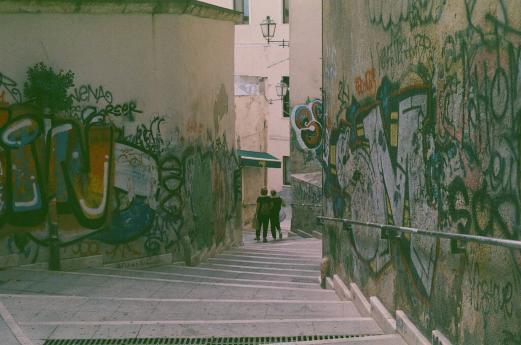 Ext. Day. Photo from the top of some stairs going down a little alley in Cagliari. The walls surrounding the stairs are covered in layer after layer of graffiti. Almost at the bottom of the stairs, a couple of middle-aged women are walking with shopping bags. The film used for this photo was expired so all the colours look paler.
