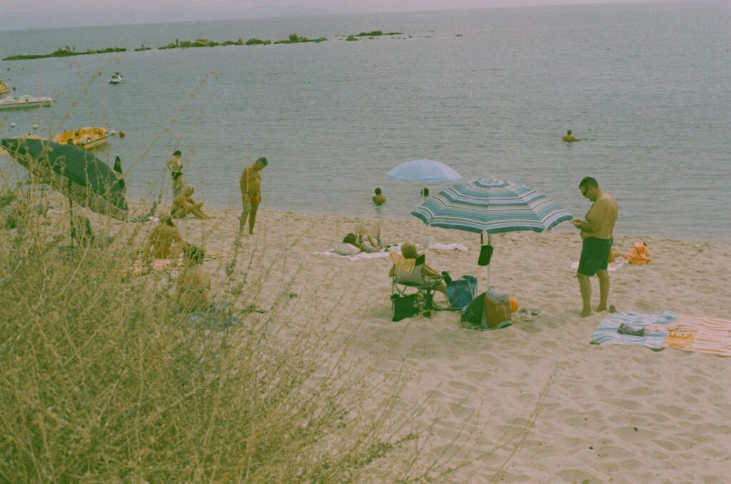Ext. Day. Photo of a Sardinian beach. In the foreground, a very dry bush covers part of the photo. Otherwise, what there is is a various arrange of working class Italian families enjoying their time at the sea. The film used for this photo was expired so all the colours look paler.