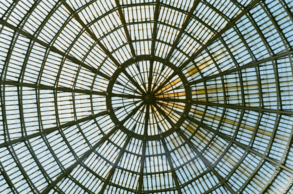 """Int. Day. Photo of the bottom of a glass and metal dome from inside Galleria Umberto I in Naples. The general look of the dome is quite rusty. The photo looks quite symmetrical, but there's an excess of rust on the right-hand side that """"ruins"""" the visual simmetry."""
