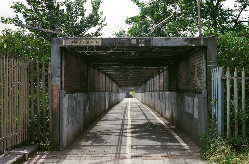 Ext. Day. Photo of a pedestrian tunnel on top of a bridge standing above a railroad. The general look it's rusty, old, and not very well maintained. It is surrounded by trees and grass. You would never walk through it overnight if you want to still be alive the next day.