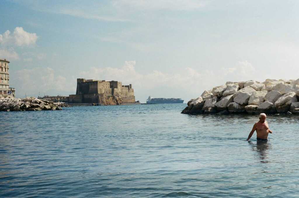 Ext. Day. Photo of a portion of the gulf of Naples. The main and central focus is the sea/water. In the background, we can see  container ship passing right behind Castel dell'Ovo. In the foreground, a bunch of white wave-breaking rocks and an old man walking in the water, naked chest.