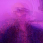 Selfies of an hairless person wearing a funky shirt. All of the selfies are overlaid and the whole picture has a purple haze kind of veil applied over it. It gives it an acid dreamy vibe, beside making it impossible to see who the actual person portrayed in it is.